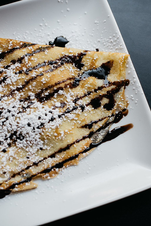 This is a picture of a pastry with chocolate syrup and powdered sugar drizzled on top