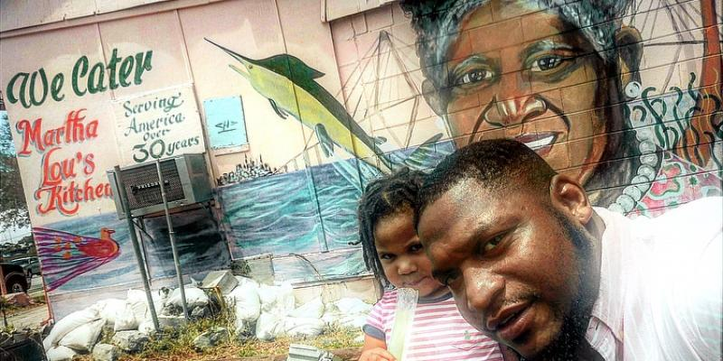 This is a picture of a black man and his young, black daughter, both wearing pink shirts, posing outside in front of a mural of Martha Lou Gadsden at Martha Lou's Kitchen restaurant in Charleston, SC.