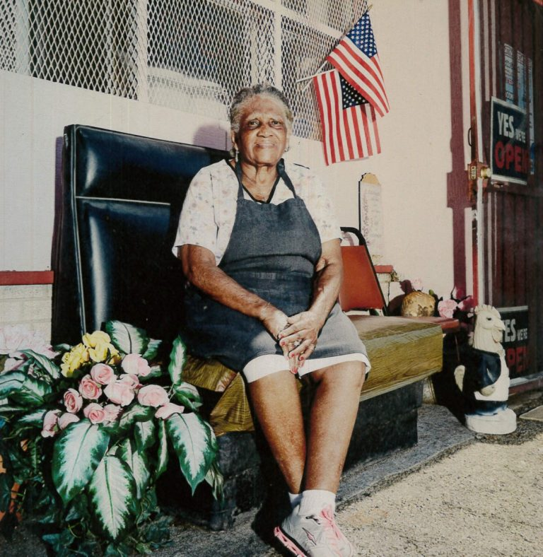 This is a picture of Martha Lou Gadsden, an elderly black woman, sitting on a bench outside in front of her restaurant, Martha Lou's Kitchen, in Charleston, SC.
