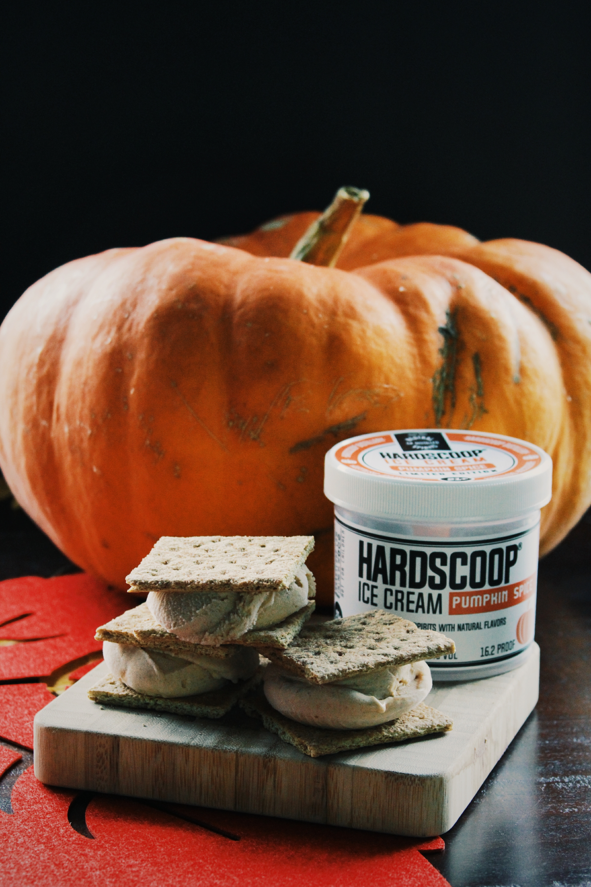 This is a picture of a pumpkin with pumpkin spice ice cream sandwiches on a wooden cutting board.