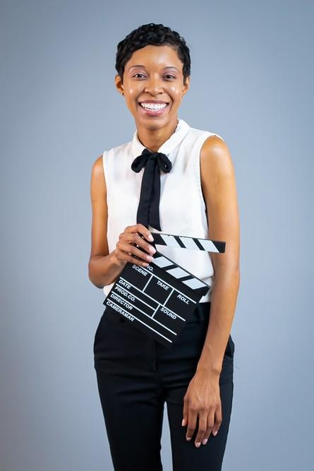 This is a picture of a black woman filmmaker named Stacie Davis wearing a white sleeveless blouse and black slacks with black high heel shoes holding a director's cut board.