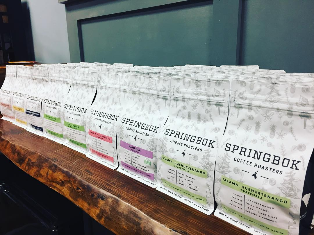 This is a picture of bags of Springbok Coffee Roasters' specialty coffees lining a wooden shelf. The bags of coffee are white with black lettering.