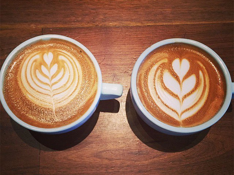 This is an overhead flat lay shot of the foam art in two white cups of coffee. The cups are sitting on top of a wooden table and show coffee with foam inside.