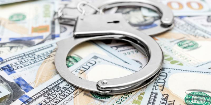 This is a picture of money spread out on a table with a pair of handcuffs on top of it.