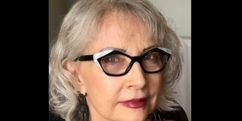 This is the headshot for the author Mirinda Kossoff. She has grey hair and is wearing black rimmed glasses.