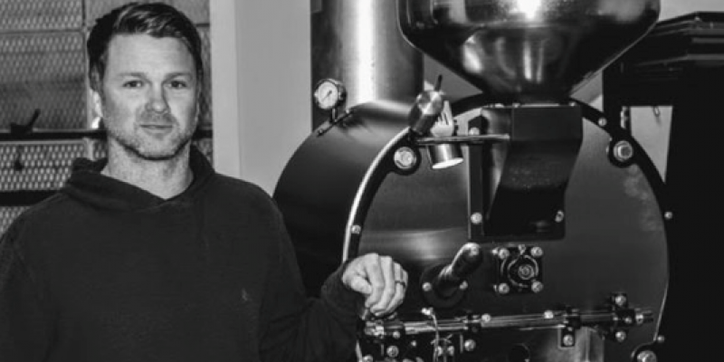 This is a black and white photo of Springbok Coffee Roasters co-owner Jason Bell standing beside a grinder. He's wearing a sweatshirt and jeans.