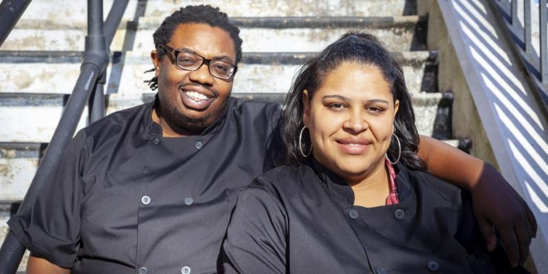 This is an image of Nathan and Chasity Brown of Daddy's Girl Bakery sitting on steps wearing black chef jackets. Nathan has his arm around Chasity.