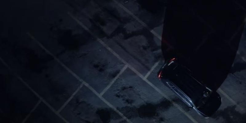 This is an ariel overhead shot of a parking lot and the top of a car at night with headlights shining.